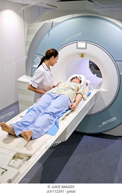 Technician nurse preparing patient for MRI scan in hospital