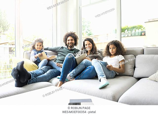 Happy family sitting on couch, reading books