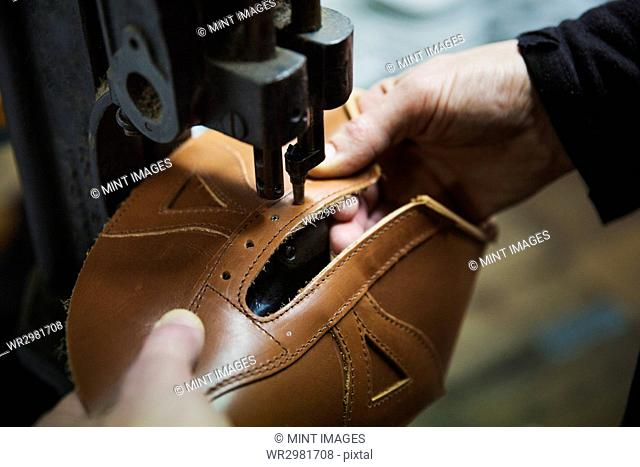 Close up of worker in a shoemaker's workshop, using a machine to punch holes into a leather shoe