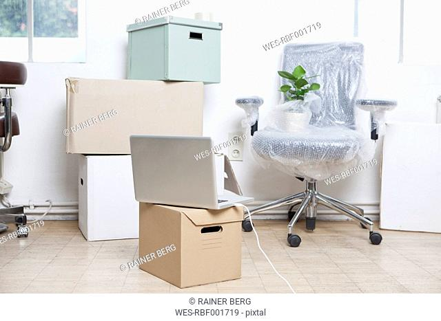 Stack of cardboard boxes, wrapped swivel chair and a notebook in an office