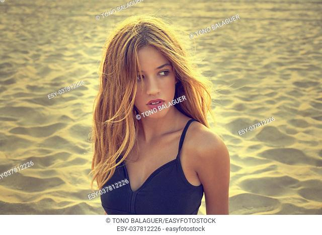 Blond teen girl portrait on the summer beach sand filtered image