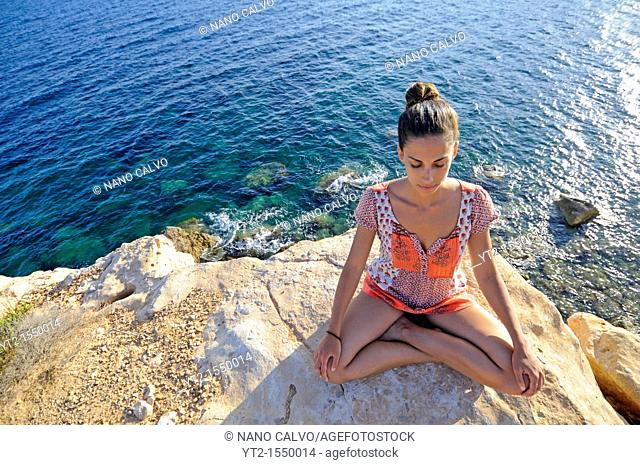 Young woman meditating in Lotus yoga pose, on a mountain