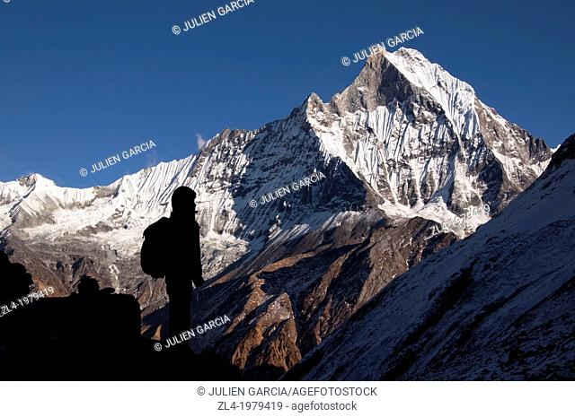 Silhouette of a trekker in front of the holy Machapuchare mountain viewed from the Annapurna Base Camp. Nepal, Gandaki, Annapurna, Annapurna Base Camp