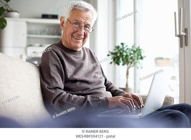 Portrait of smiling senior man sitting on couch at home using laptop