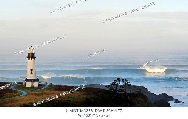 The historic Yaquina Head tower lighthouse on a headland overlooking the Pacific coastline