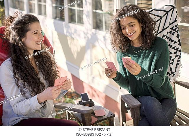Two young female friends laughing, playing card game on patio