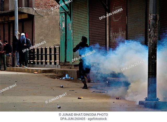 kashmiri Muslim protester running away from tear gas shell, baramulla, Kashmir, India, Asia
