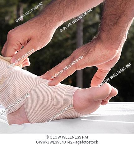 Doctor tying crepe bandage on a patient's foot