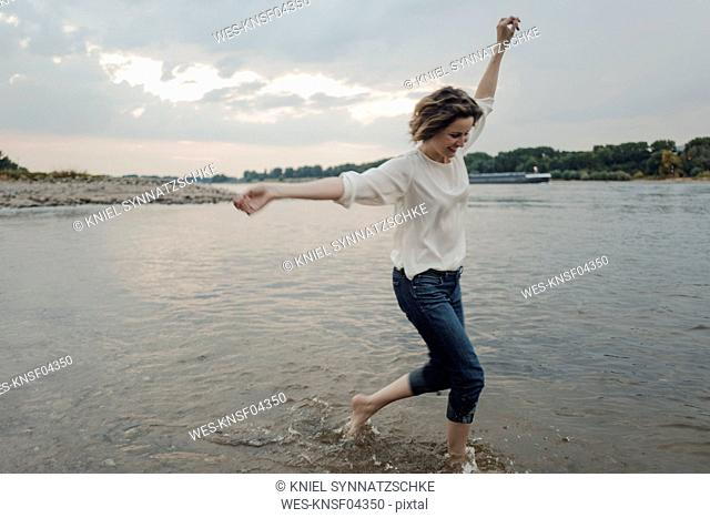 Laughing woman running at the riverside