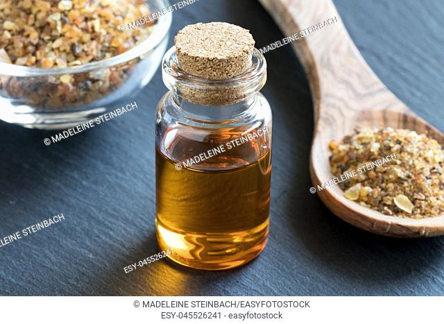 A bottle of myrrh essential oil with myrrh resin on a dark background