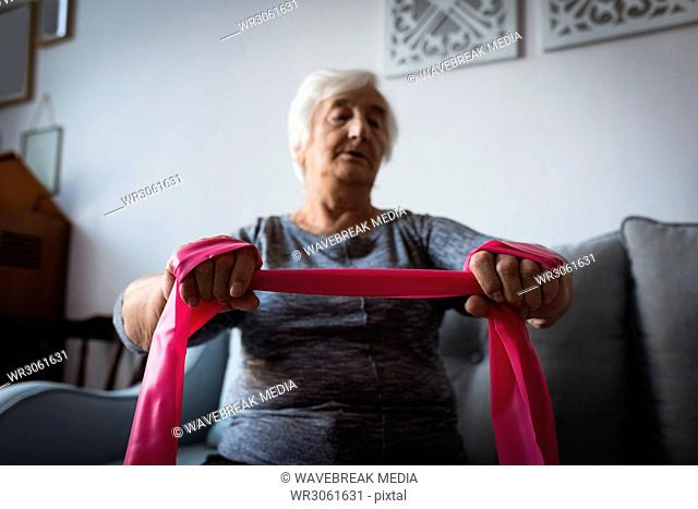 Senior woman performing exercise with resistance band in living room