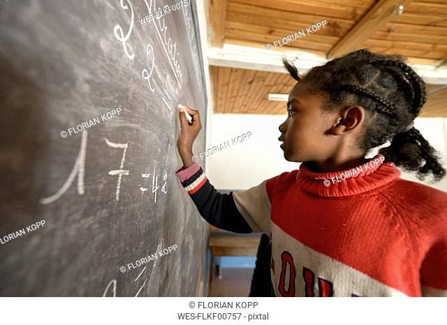 Madagaskar, Girl in Fianarantsoa elementary school calculatiing at blackboard