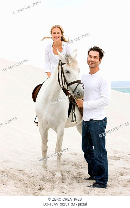 Woman and man with horse on the beach