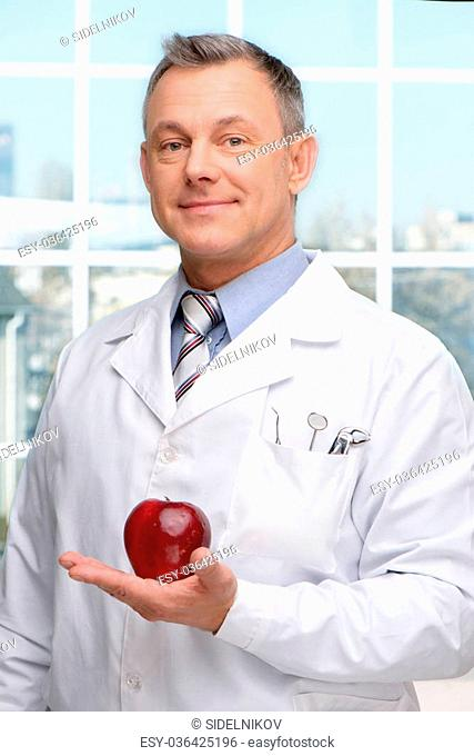 Photo of dentist holding red apple and looking at camera. Concept for teeth hygiene