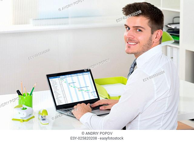 Young Happy Businessman Working With Gantt Chart On Laptop At Desk
