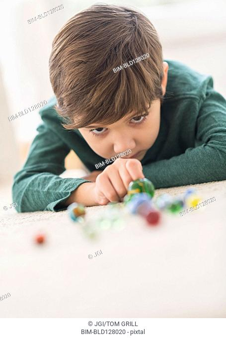 Hispanic boy playing with marbles on floor