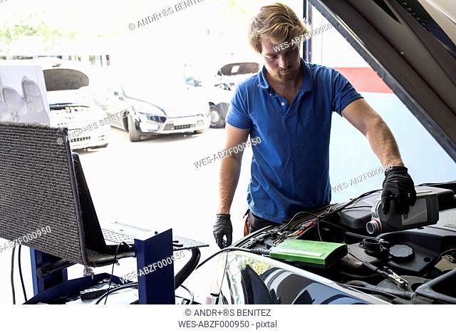 Mechanic refilling oil in a car