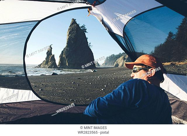 Man sitting in camping tent, Rialto Beach in distance, Olympic National Park, Washington, USA