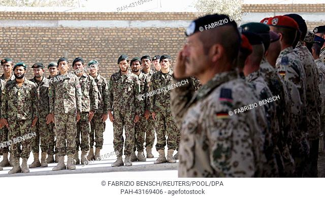 Members of the Afghan National Civil Order Police (ANCOP), Afghan Armed Forces and German armed Bundeswehr forces attend the handover ceremony of a German base...