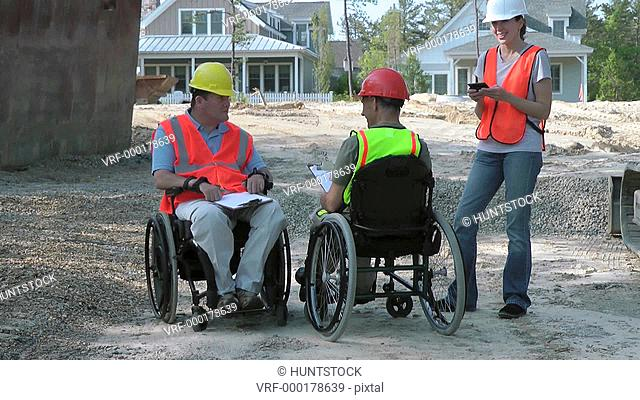 Construction engineers discussing site issues using smart phone, men in wheelchairs with spinal cord injuries