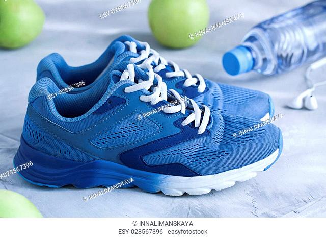 Sport shoes, bottle of water, apples on gray concrete background. Concept healthy lifestyle, sport and diet. Focus is only on the sneakers