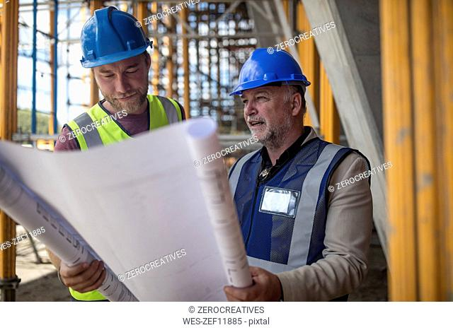 Engineers on construction site discussing blueprint
