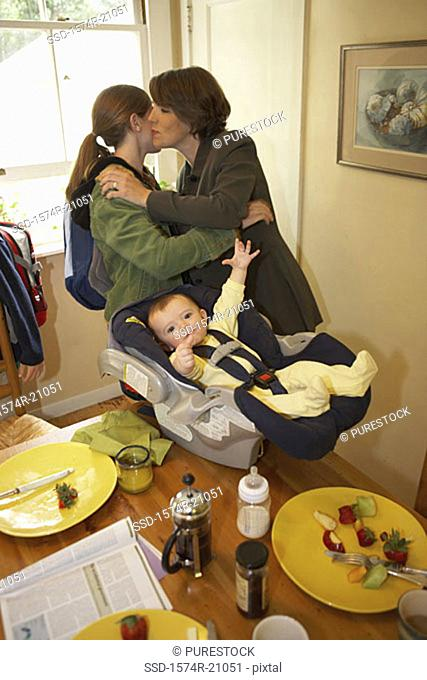 Side profile of a mid adult woman kissing her daughter with her son in a baby seat beside them