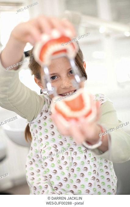 Germany, Bavaria, Landsberg, Girl 8-9 holding model of teeth, smiling, portrait