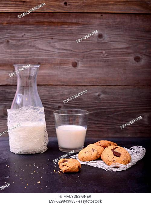 Stack of Chocolate chip cookie with bottle and glass of milk on black background