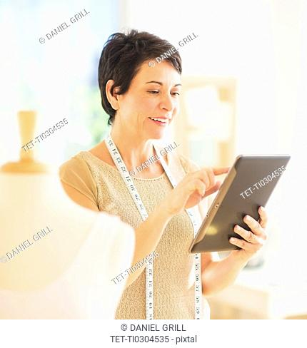 Portrait of mature woman with clothing bust using digital tablet