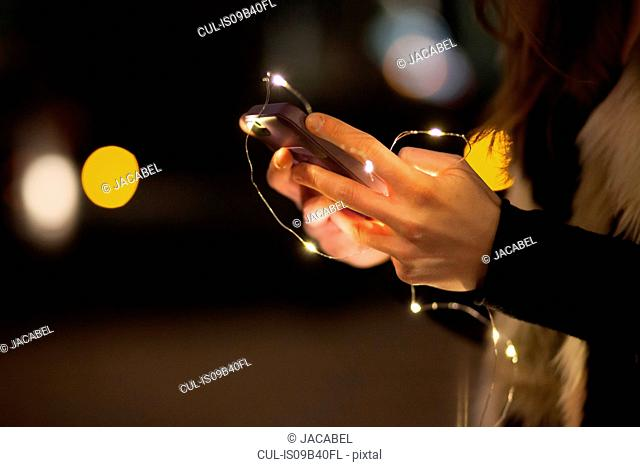 Young woman holding mobile phone and lights, close up of hand
