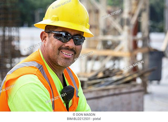 Hispanic worker smiling at construction site