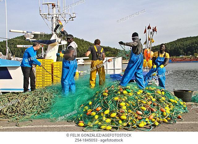 Fishermen pick up nets in Aviles harbour, Asturias, Spain