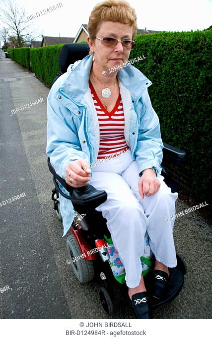 Older woman wheelchair user going down the road