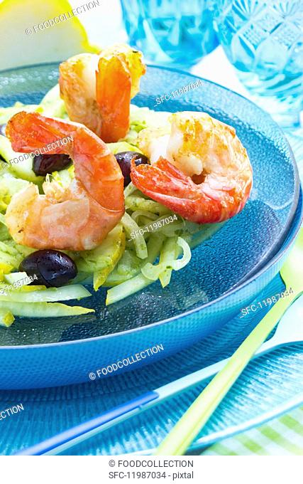 King prawns on a lemon and fennel salad with black olives on a glass turquoise plate