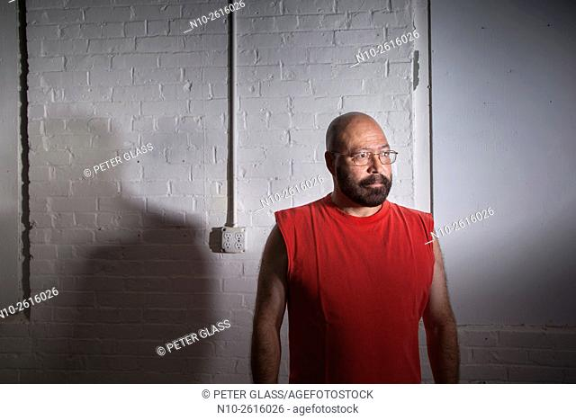 Middle age bald man with a beard and wearing glasses