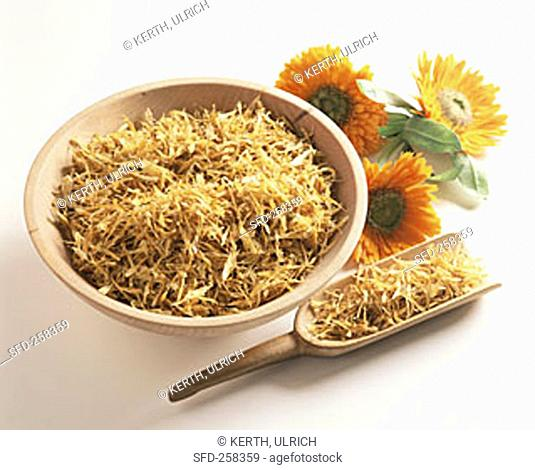 Marigold tea in wooden bowl and on scoop