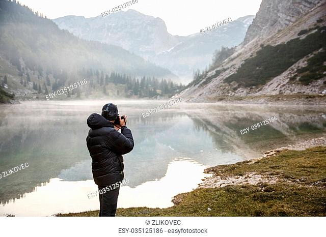 Photographer on assignment, holding a camera, taking photos of beautiful mountain landscape in the morning by a mountain lake with winter mist covered surface