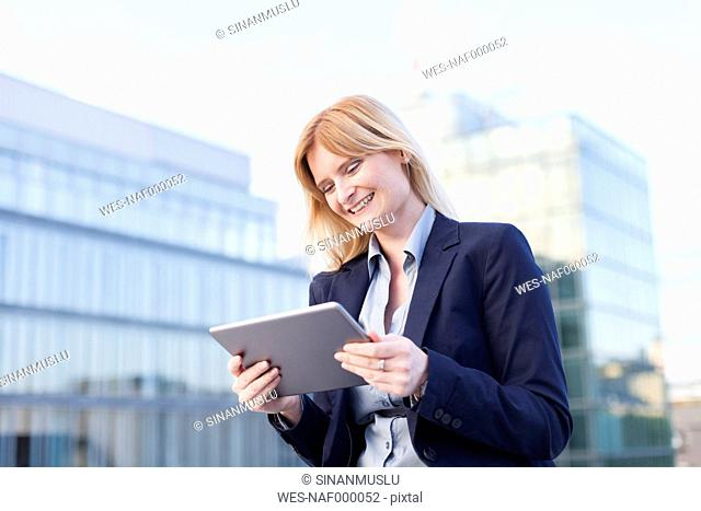 Content businesswoman looking at tablet
