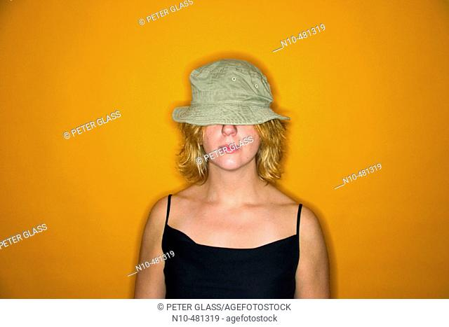 Young blond woman wearing a hat that covers her eyes