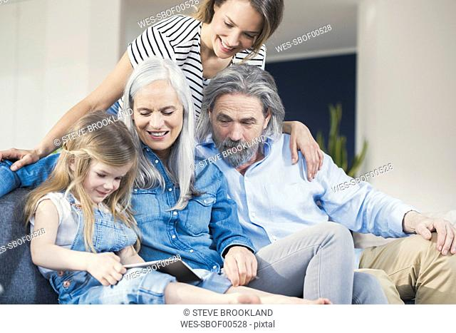 Family sitting on couch, watching granddaughter use tablet pc