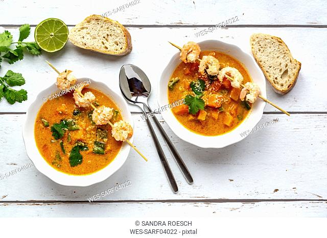 Two bowls of sweet potato soup with shrimps, coconut flakes and fresh coriander