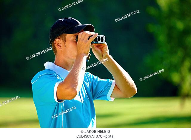 Mid adult man wearing baseball cap looking through binoculars