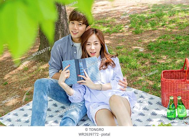 Young smiling couple having picnic at park