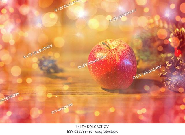 christmas, decoration, holidays and new year concept - close up of red apple with fir branch decoration on wooden table over lights