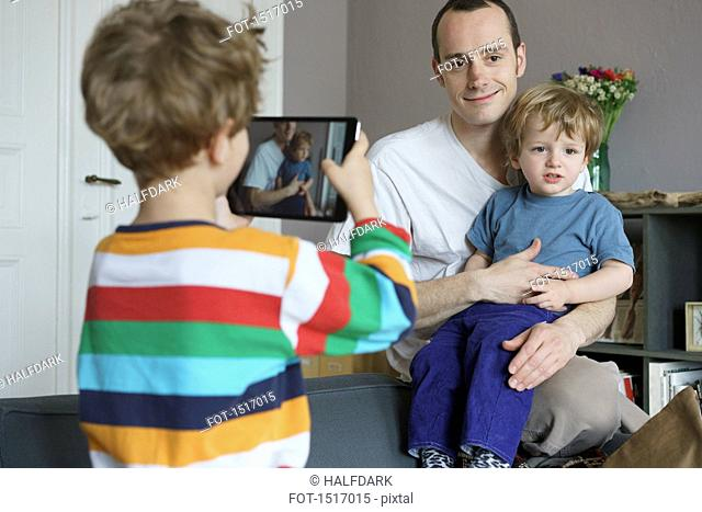 Boy photographing family through digital tablet at home
