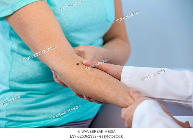 Dermatologist examines a mole of female patient