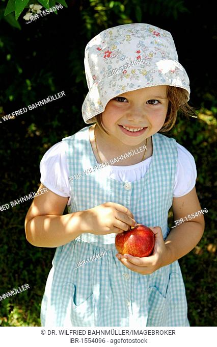 Little girl in the summer with an apple