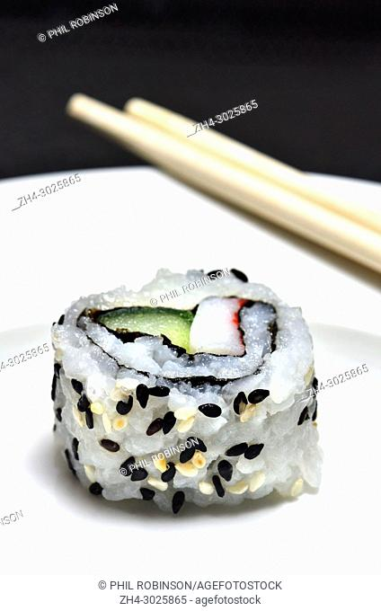Sushi on a white plate: uramaki (roll with rice on the outside) and chopsticks