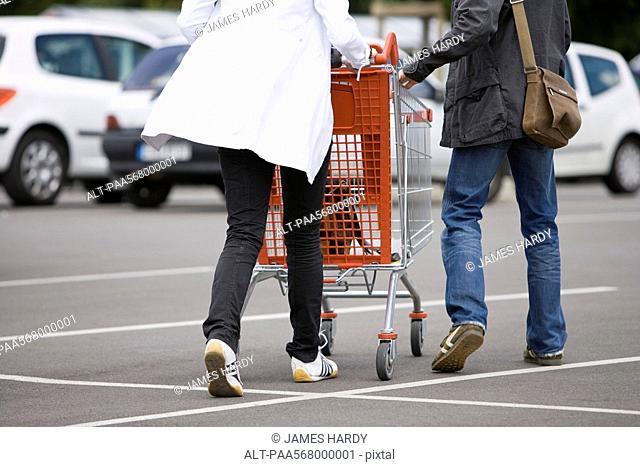 Shoppers pushing shopping cart in parking lot